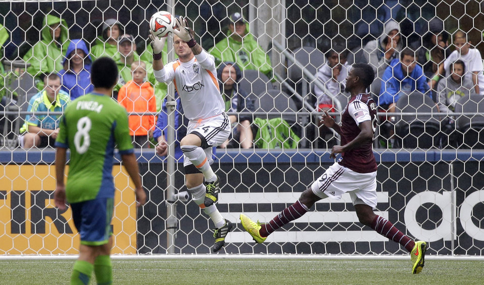 Photo - Seattle Sounders goalkeeper Stefan Frei, center, jumps to make a save as Colorado Rapids' Edson Buddle, right, and Sounders' Gonzalo Pineda (8) look on in the second half of an MLS soccer match, Saturday, Aug. 30, 2014, in Seattle. The Sounders beat the Rapids, 1-0. (AP Photo/Ted S. Warren)