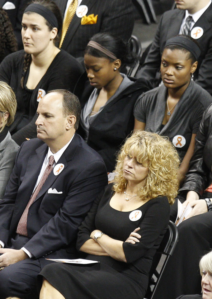 Photo - Oklahoma women's basketball coach Sherri Coale, right, sits with Oklahoma athletic director Joe Castiglione, left, and members of her team, at rear, during a memorial service in Stillwater, Okla., Monday, Nov. 21, 2011. Oklahoma State women's basketball Kurt Budke and assistant women's basketball coach Miranda Serna were killed along with pilot Orlin Branstetter and his  wife, Paula Branstetter, in a plane crash last Thursday.  (AP Photo/Sue Ogrocki) ORG XMIT: OKSO119