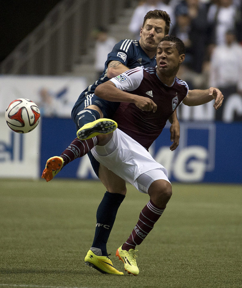 Photo - Vancouver Whitecaps FC Jordan Harvey fights for control of the ball with Colorado Rapids FC Gabriel Torres during first half of MLS soccer action in Vancouver, Canada, Saturday, April 5, 2014. (AP Photo/The Canadian Press, Jonathan Hayward)