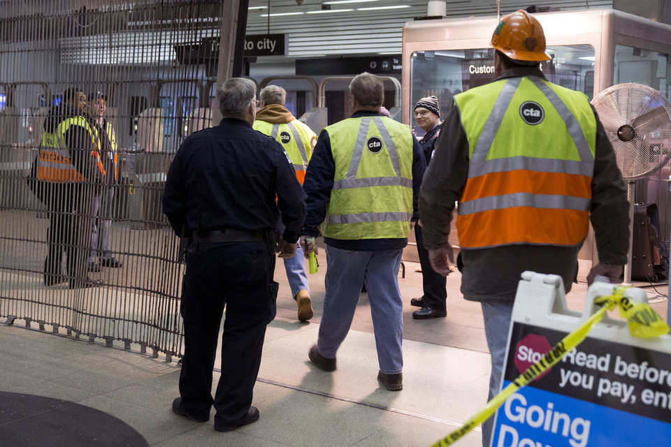 Photo - Chicago Transit Authority employees work the scene where a Chicago Transit Authority derailed at the O'Hare Airport station early Monday, March 24, 2014, in Chicago. More than 30 people were injured after the eight-car train plowed across a platform and scaled an escalator at the underground station. (AP Photo/Andrew A. Nelles)