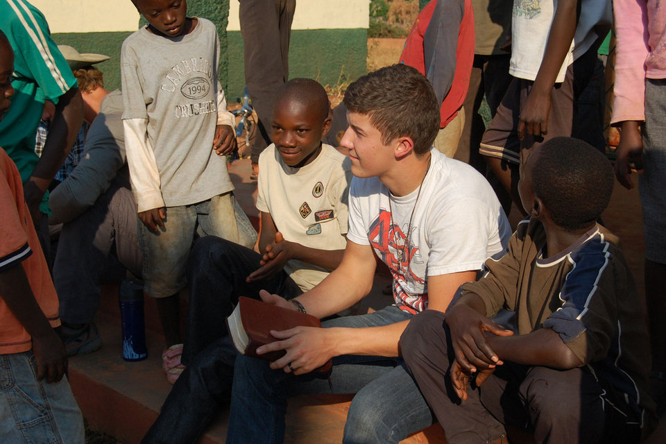Oklahoma Baptist University student Joseph Hefner, right center, a sophomore youth ministry major from Denison, Texas, leads a Bible study for the children of the New Day Orphanage in Mapanza, Zambia. Photo Provided