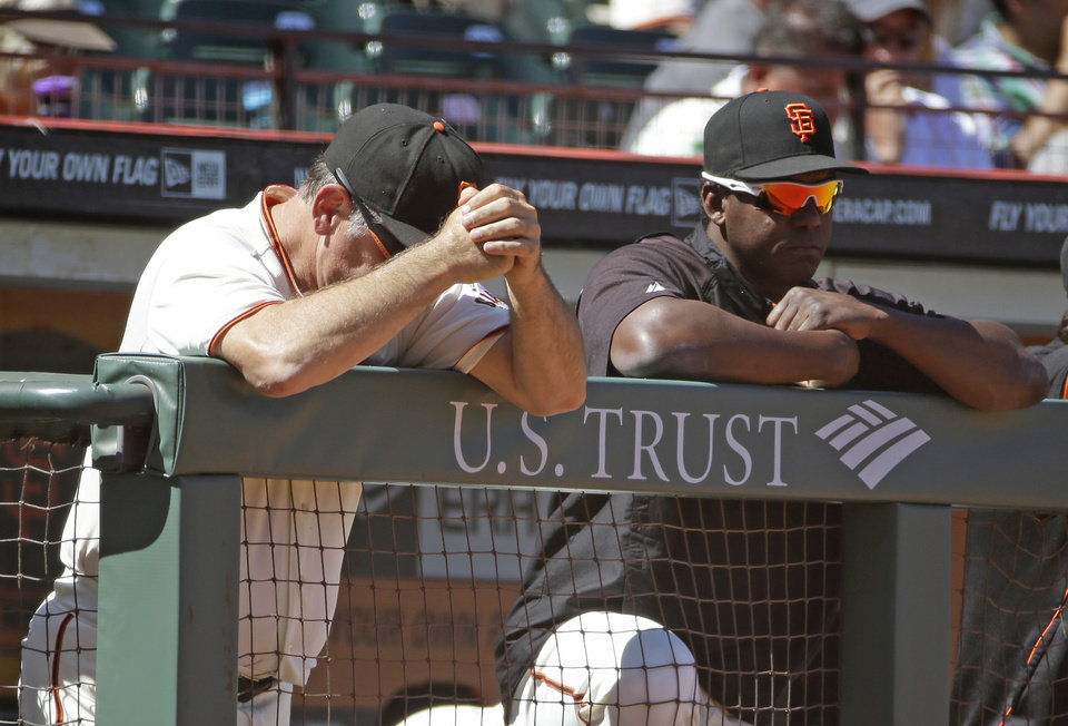 Photo - San Francisco Giants manager Bruce Bochy, left, and hitting coach Hensley Meulens, right, rest on the dugout railing in the ninth inning of their baseball game against the St. Louis Cardinals, Thursday, July 3, 2014, in San Francisco. St. Louis won the game 7-2. (AP Photo/Eric Risberg)