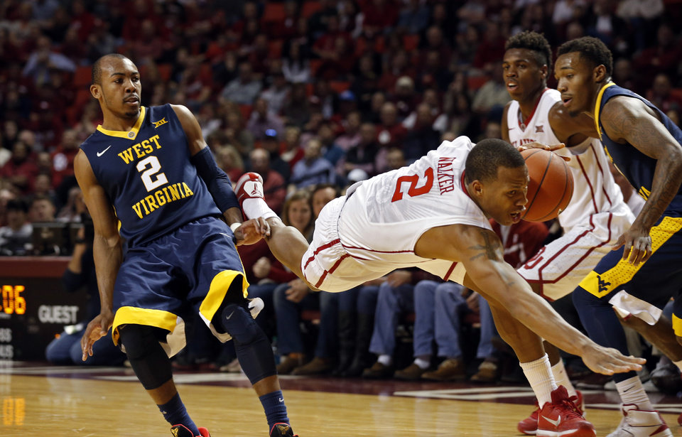 Photo - Oklahoma's Dinjiyl Walker (2) flies through the air after colliding with West Virginia's Jevon Carter (2) as the University of Oklahoma Sooner (OU) men play the West Virginia Mountaineers (WV) in NCAA, college basketball at The Lloyd Noble Center on Jan. 16, 2016 in Norman, Okla. Photo by Steve Sisney, The Oklahoman