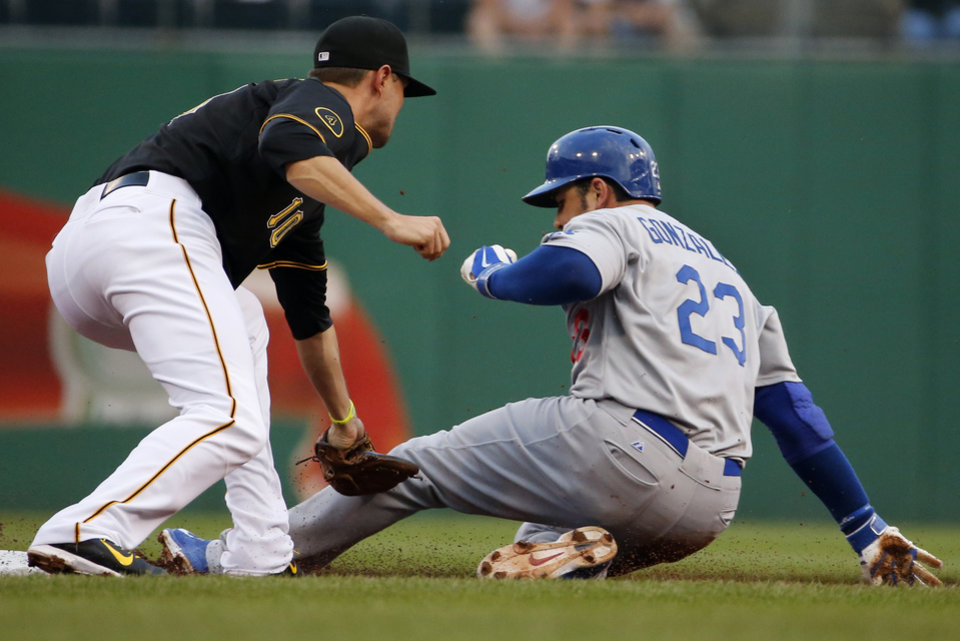 Photo - Los Angeles Dodgers' Adrian Gonzalez (23) steals second ahead of the tag by Pittsburgh Pirates shortstop Jordy Mercer (10) during the first inning of a baseball game in Pittsburgh Monday, July 21, 2014. (AP Photo/Gene J. Puskar)