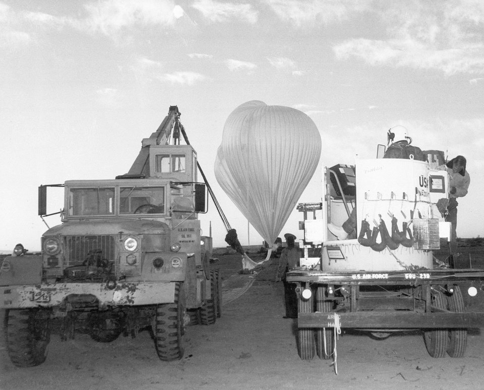 Photo -   FILE- In this Nov. 16, 1959, file photo, provided by the U.S. Air Force, Capt. Joseph Kittinger Jr. waits in the open balloon gondola, right, while the two million cubic-foot polyethylene balloons are filled with helium for the Excelsior I test jump at White Sands Missile Range, N.M. Kittinger made the first free-fall parachute jump at an altitude of 76,400 feet, setting a record. On Tuesday, Oct. 9, 2012, if winds allow, in the desert surrounding Roswell, N.M., pilot Felix Baumgartner will attempt to break Kittinger's world record for the highest and fastest free fall. (AP Photo/U.S. Air Force, File)