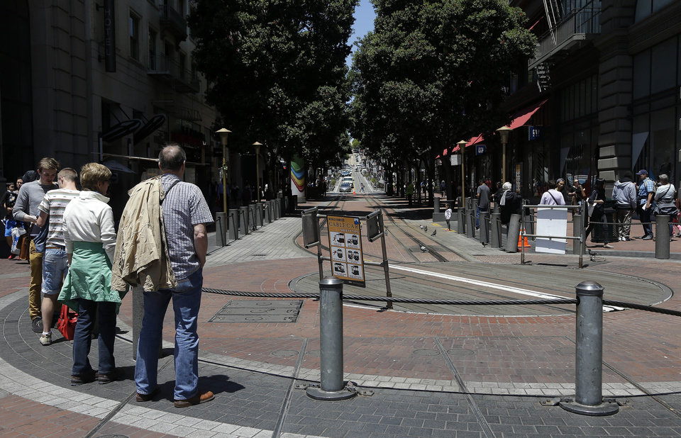 Photo - A group of pedestrians stand at the Powell Street cable car turnaround in San Francisco, Tuesday, June 3, 2014. The city's famed cable cars were halted for a second straight day, and the rest of the transit system experienced delays after drivers called in sick again on Tuesday, days after overwhelmingly rejecting a new labor contract, officials said. (AP Photo/Jeff Chiu)