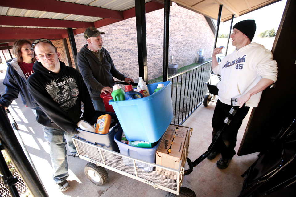 Members of the Memorial Baptist Church in Fond du Lac, Wis.,  came to McLoud to help at the food pantry at the Emmanuel Baptist Church. Christine Popp, Matt Duley, Rick Behlke and Pastor Brian Hastings roll a cart full of food into the pantry for sorting on Wednesday. <strong>David McDaniel - The Oklahoman</strong>