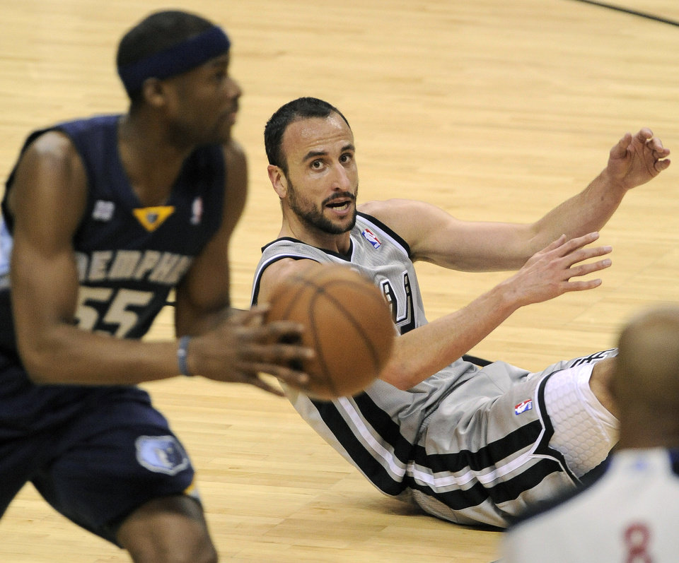 Photo - San Antonio Spurs' Manu Ginobili, right, of Argentina, looks on as Memphis Grizzlies' Keyon Dooling recovers the loose ball during the first half of Game 1 of the Western Conference final NBA basketball playoff series, Sunday, May 19, 2013, in San Antonio. (AP Photo/Darren Abate)