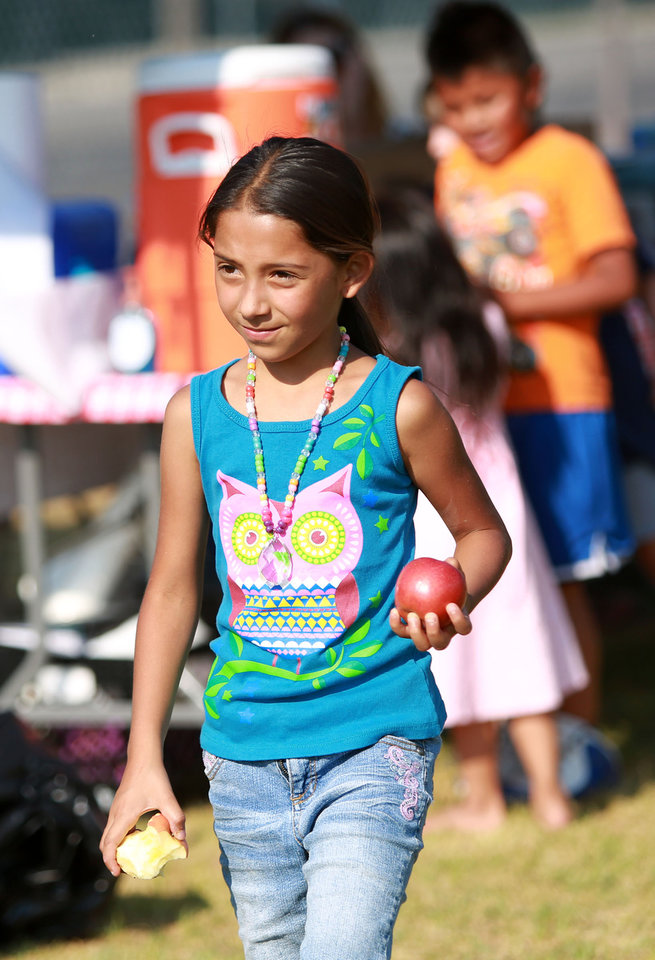 Photo -       Adriana Garcia gets an apple after dinner outside of the Central Park Community Center in South Salt Lake on Friday, July 18, 2014. The dinner is part of the Salt Lake CAP summer food program, which offers free dinner to children at five locations in the valley, Monday through Friday.