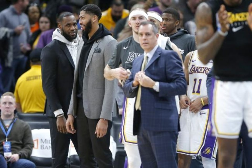 Photo -  LeBron James, left, and Anthony Davis watch during the final minute of the Lakers' 125-110 win against the Thunder on Saturday at Chesapeake Energy Arena. [Bryan Terry/The Oklahoman]