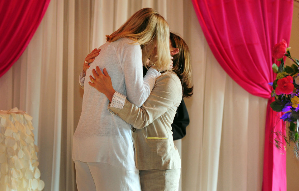 Photo - Julie Engbloom, left, and Laurie Brown kiss each other after getting married at the Melody Ballroom in Portland, Ore. on Monday, May. 19, 2014. Federal Judge Michael McShane released an opinion on Oregon's Marriage Equality lawsuit that grants gay and lesbian couples the freedom to marry in Oregon. (AP Photo/Steve Dykes)