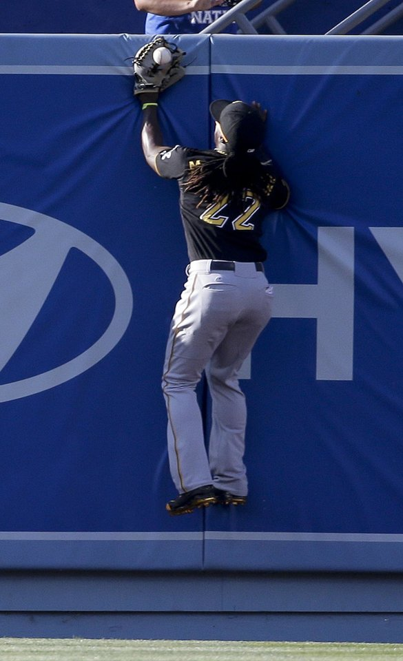 Photo - Pittsburgh Pirates center fielder Andrew McCutchen can't a glove on a ball that went for a two-run triple by Los Angeles Dodgers' Drew Butera during fourth inning of a baseball in Los Angeles, Saturday, May 31, 2014. (AP Photo/Chris Carlson)