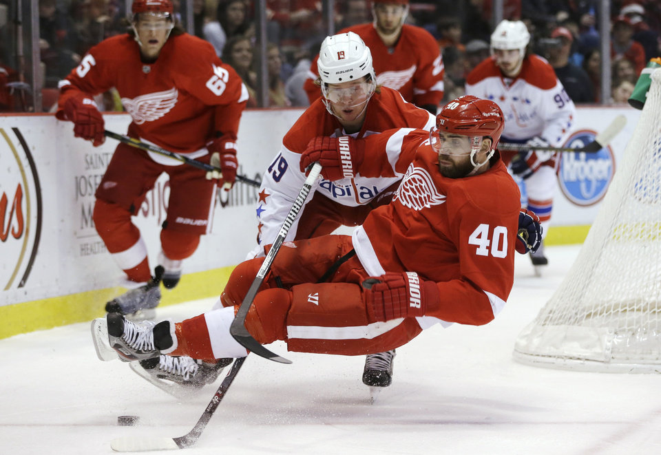 Photo - Detroit Red Wings left wing Henrik Zetterberg (40) of Sweden is tripped by Washington Capitals center Nicklas Backstrom (19), of Sweden, during the first period of an NHL hockey game in Detroit, Friday, Jan. 31, 2014. (AP Photo/Carlos Osorio)