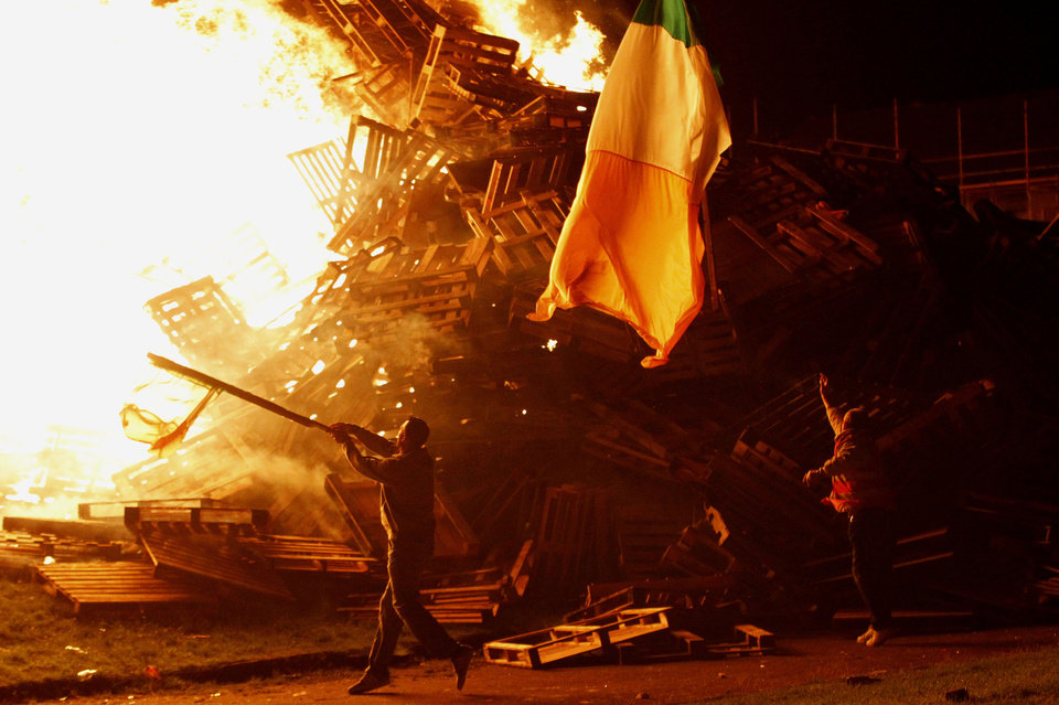 Photo -   Protestants throw an Irish flag onto a massive bonfire in the Shankill Estate, West Belfast, Northern Ireland, Thursday, July 12, 2012. Thousands of bonfires have been set on fire in Protestant areas across Northern Ireland for the annual July 12th celebrations to remember the 1690 battle of the Boyne where the Protestant King William of Orange defeated the Catholic King James. (AP Photo/Peter Morrison)