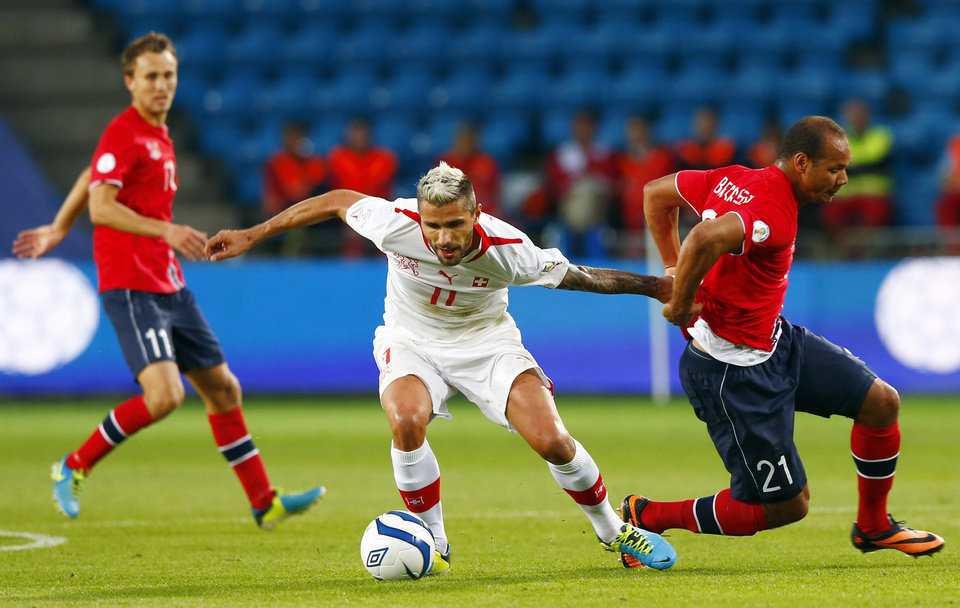 Photo - Switzerland's Valon Behrami, center, controls the ball between Norway's Daniel Braaten, right, and Magnus Wolff Eikrem during their World Cup 2014 qualifying soccer match in Ullevaal staium in Oslo, Tuesday Sept. 10, 2013. (AP Photo/Hakon Mosvold Larsen, NTB Scanpix) NORWAY OUT