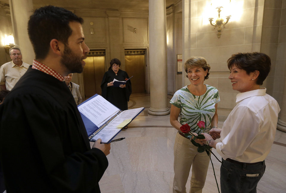 Photo - Marriage commissioner Jared Scherer, left, officiates as Pam Shaheen, center, marries Mary Beth Gabriel at City Hall in San Francisco, Friday, June 28, 2013. A three-judge panel of the 9th U.S. Circuit Court of Appeals issued a brief order Friday afternoon dissolving,