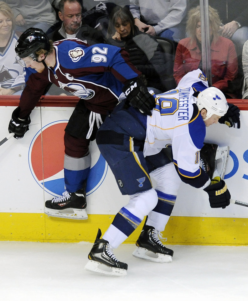Photo - St. Louis Blues defenseman Jay Bouwmeester, right, checks Colorado Avalanche left wing Gabriel Landeskog, left, into the boards in the first period of an NHL hockey game on Saturday, March 8, 2014, in Denver. (AP Photo/Chris Schneider)