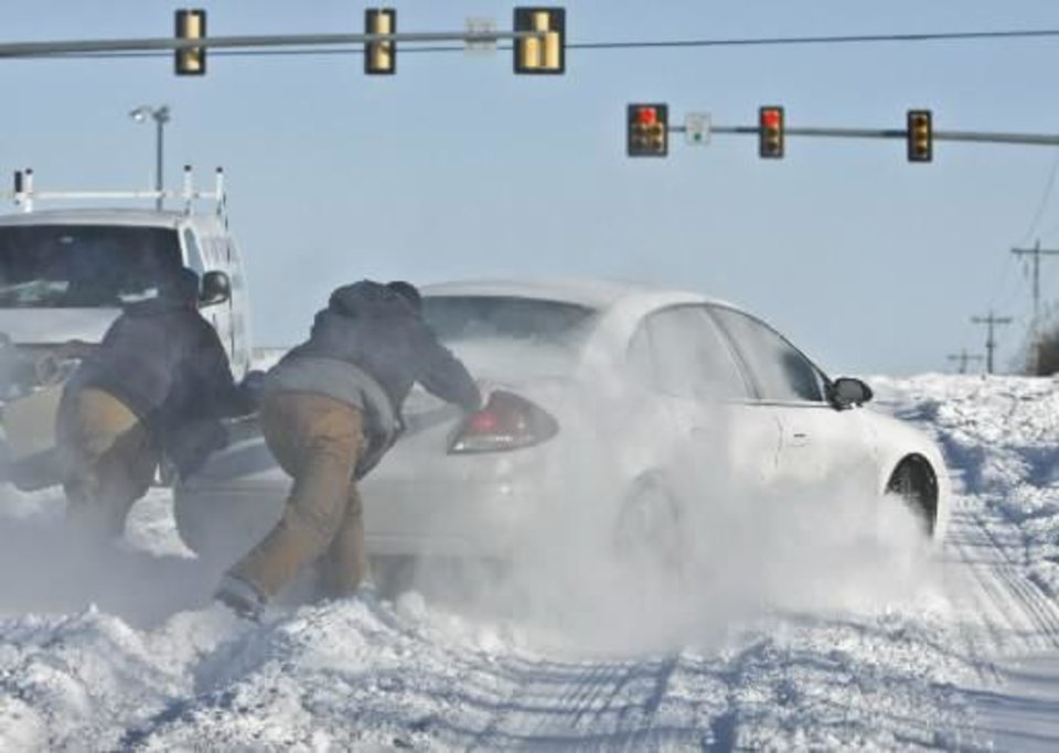 A couple of Good Samaritans help push a driver out of the deep snow on Tuesday, Feb. 2, 2011, Oklahoma City, Okla. Photo by Chris Landsberger