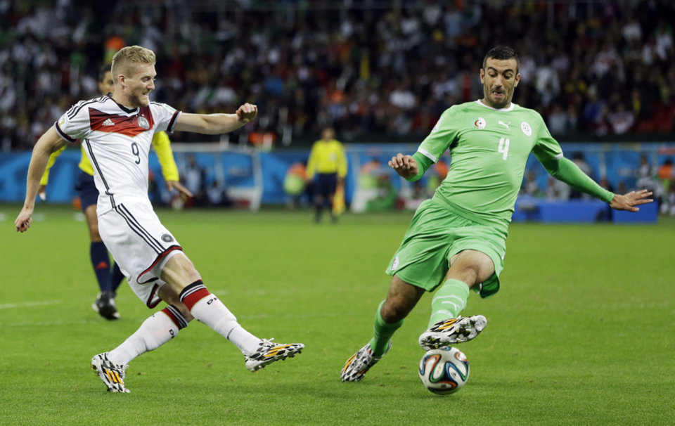 Photo - Germany's Andre Schuerrle, left, takes a shot past Germany's Benedikt Hoewedes during the World Cup round of 16 soccer match between Germany and Algeria at the Estadio Beira-Rio in Porto Alegre, Brazil, Monday, June 30, 2014. (AP Photo/Kirsty Wigglesworth)
