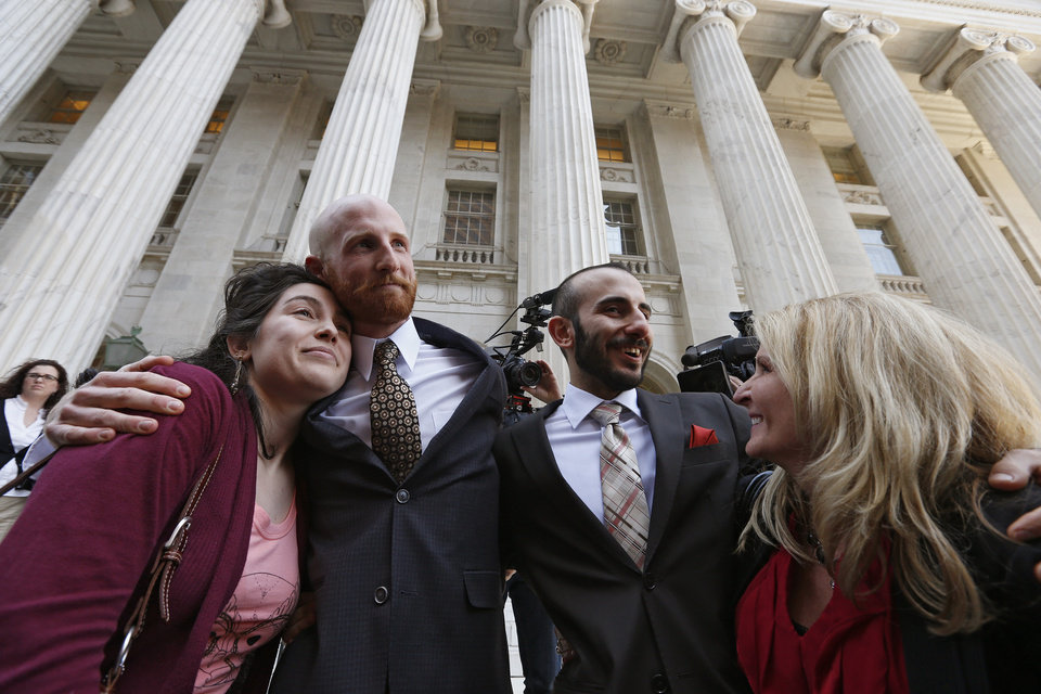 Photo - Plaintiff and gay rights activist Derek Kitchen, center left, hugs his cousin Amelia Davis, left, as Derek's partner Moudi Sbeity hugs his mother Joni Jensen, after leaving court following a hearing at the U.S. Circuit Court of Appeals in Denver, Thursday, April 10, 2014. The court is to decide if it agrees with a federal judge in Utah who in mid-December overturned a 2004 voter-passed gay marriage ban, saying it violates gay and lesbian couples' rights to due process and equal protection under the 14th Amendment. (AP Photo/Brennan Linsley)