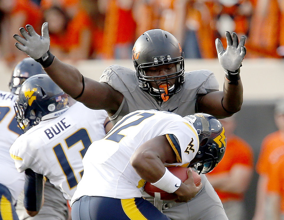Photo - Oklahoma State's Anthony Rogers (94) pressures West Virginia's Geno Smith (12) during a college football game between Oklahoma State University (OSU) and the West Virginia University at Boone Pickens Stadium in Stillwater, Okla., Saturday, Nov. 10, 2012. OSU won 55-34. Photo by Sarah Phipps, The Oklahoman