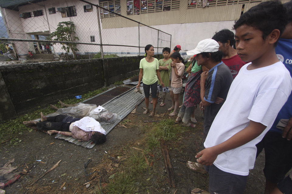 Photo - Residents look at bodies recovered from flashflood in New Bataan, Compostela Valley province, southern Philippines on Wednesday Dec. 5, 2012. The death toll from Typhoon Bhopa climbed to more than 100 people Wednesday, while scores of others remain missing in the worst-hit areas of the southern Philippines. (AP Photo/Karlos Manlupig)