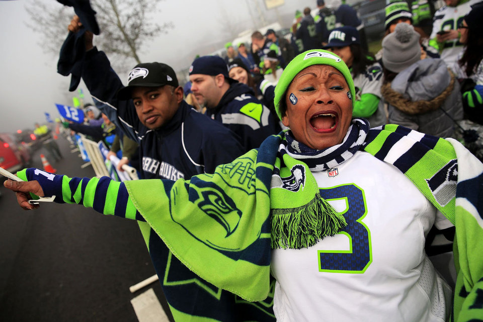 Photo - Marcia Shiri-Wasto, center, cheers with Seattle football fans on South 188th Street in SeaTac, Wash. Sunday, Jan. 26, 2014. The Seahawks drove past the crowd on route to the airport for Super Bowl XLVIII. (AP Photo/The Seattle Times, Erika Schultz) OUTS: SEATTLE OUT, USA TODAY OUT, MAGAZINES OUT, TELEVISION OUT, SALES OUT. MANDATORY CREDIT TO:  ERIKA SCHULTZ / THE SEATTLE TIMES