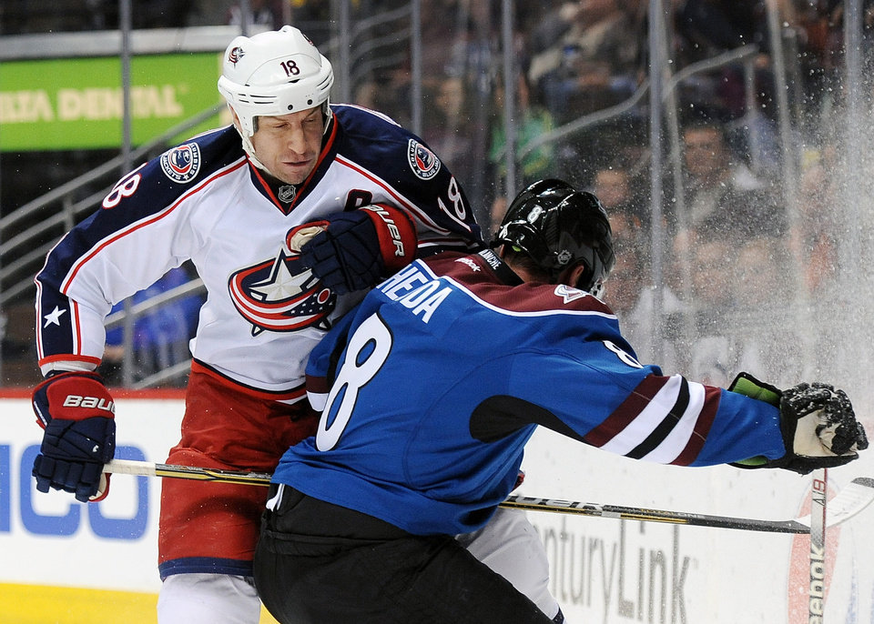 Photo - FILE - Im this, April 5, 2012 file photo, Columbus Blue Jackets left wing RJ Umberger, left, colliding with Colorado Avalanche defenseman Jan Hejda, of the Czech Republic, during the first period of an NHL hockey game in Denver. A new team president, a sort of new head coach and six or seven new faces on the roster have the Blue Jackets looking for improvement as they head into the new, shortened NHL season. (AP Photo/Chris Schneider, File)
