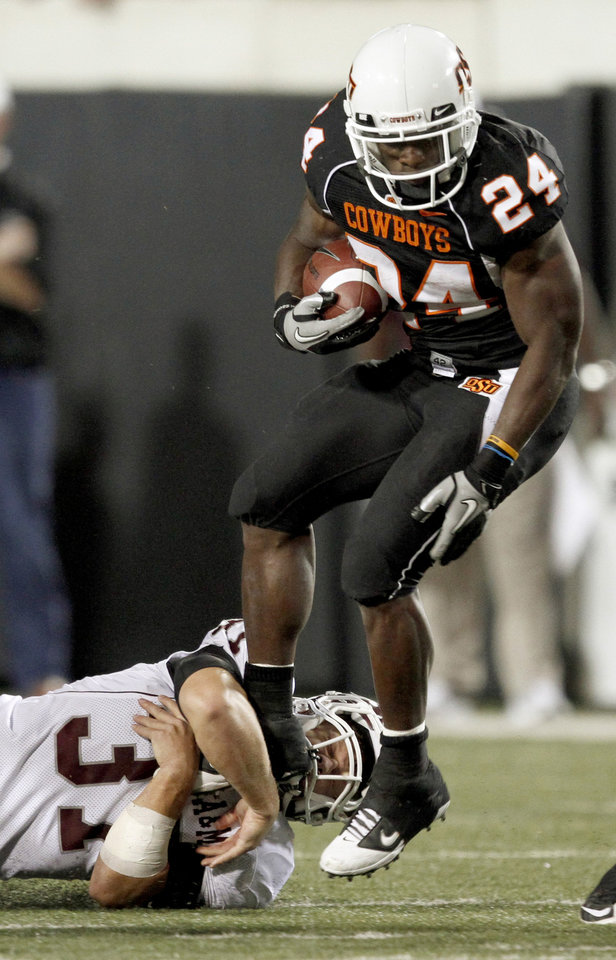 Photo - OSU's Kendall Hunter tries to get past Texas A&M's Michael Hodges during the college football game between Texas A&M University and Oklahoma State University (OSU) at Boone Pickens Stadium in Stillwater, Okla., Thursday, Sept. 30, 2010. Photo by Bryan Terry, The Oklahoman
