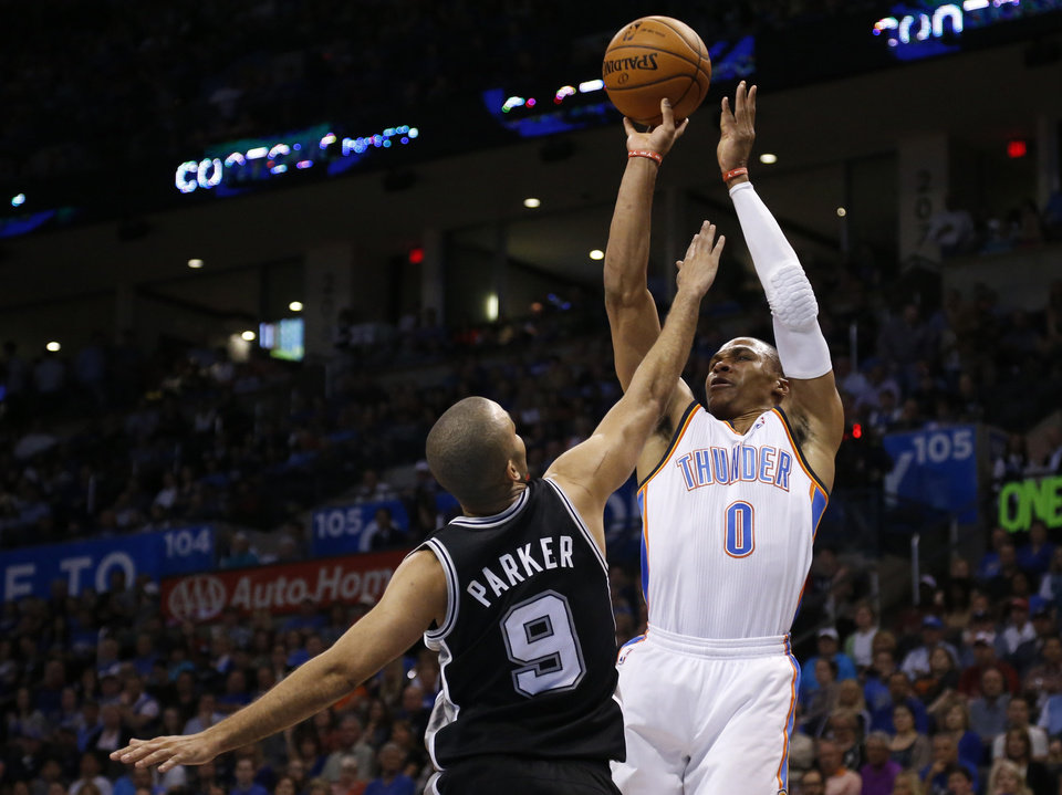 Photo - Oklahoma City Thunder guard Russell Westbrook (0) shoots over San Antonio Spurs guard Tony Parker (9) during the first quarter of an NBA basketball game in Oklahoma City, Thursday, April 3, 2014. (AP Photo/Sue Ogrocki)