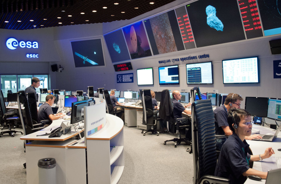 Photo - Experts watch their screens at the control center of the European Space Agency, ESA, in Darmstadt, Germany, Wednesday, Aug. 6, 2014. A mission to land the first space probe on a comet reaches a major milestone when the unmanned Rosetta spacecraft finally catches up with its quarry on Wednesday. It's a hotly anticipated rendezvous: Rosetta flew into space more than a decade ago and had to perform a series of complex maneuvers to gain enough speed to chase down comet 67P/Churyumov-Gerasimenko on its orbit around the sun. (AP Photo/dpa, Boris Roessler)