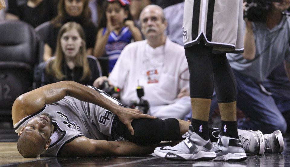 San Antonio Spurs' Tim Duncan lies on the floor after being injured on a play during the first half against the Washington Wizards during an NBA basketball game Saturday, Feb. 2, 2013, in San Antonio. The Spurs said via Twitter that Duncan sprained his right ankle and left knee and would not return to the game. (AP Photo/San Antonio Express-News, Edward A. Ornelas) SAN ANTONIO OUT