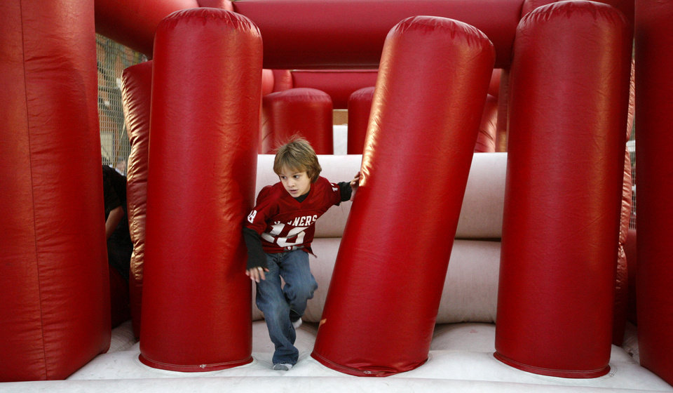 Photo - OU fan Kaleb Smith, 6, of Elmore City, Okla., plays outside the satdium before the college football game between the University of Oklahoma Sooners and Texas Tech University at Gaylord Family -- Oklahoma Memorial Stadium in Norman, Okla., Saturday, Nov. 22, 2008. BY BRYAN TERRY, THE OKLAHOMAN