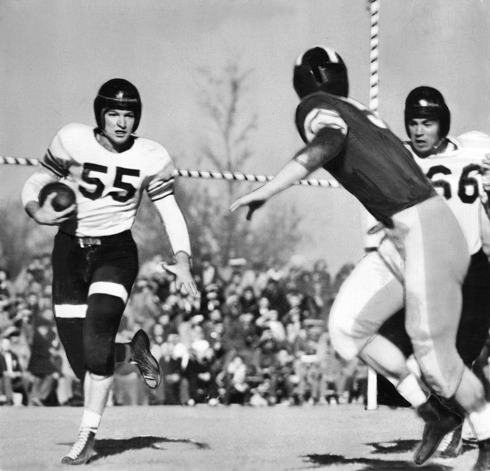 Sooner Jack Venable (dark shirt) chases All-America Bob Fenimore (55) out of bounds on the Aggie 33-yard line in the first quarter Saturday as Aggie Fullback Jimmy Reynolds (66) arrives too late to get the block that would have sent the big Blond rocketing goalward.  Fenimore plunged for one touchdown and passed for two others in Saturday's game.   Oklahoma A&M beat the University of Oklahoma (OU) Sooners, 47-0, in Norman before a crowd of 33,000.   Staff photo taken Nov. 24, 1945.