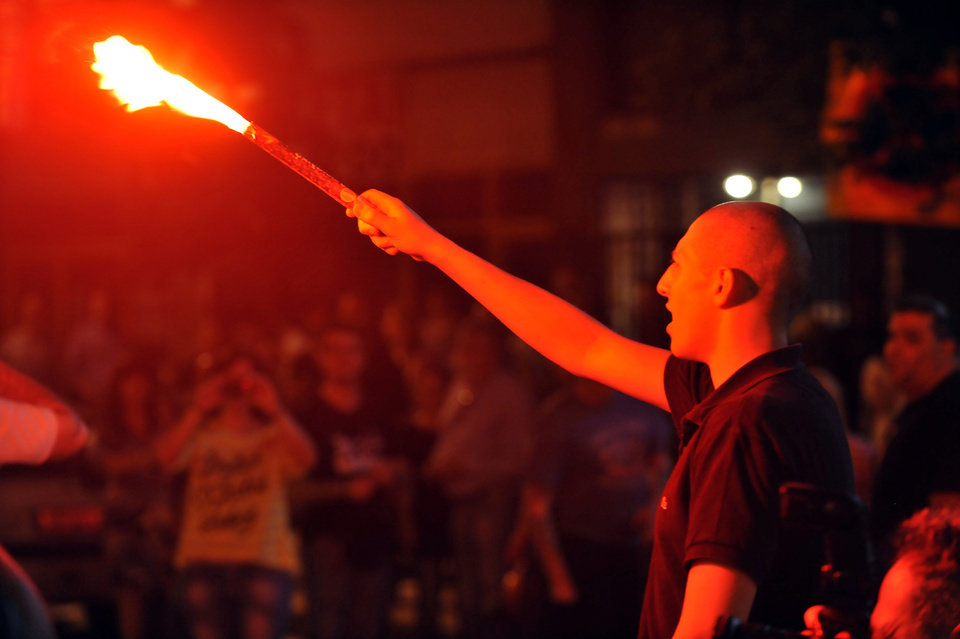 Photo -   An extreme far-right Golden Dawn party's supporter holds a flare during the elections results in the northern Greek port city of Thessaloniki, Sunday, May 6, 2012. Golden Dawn, which has vowed to kick out immigrants and mine Greece's borders with Turkey, was predicted to win between 6.5-7.5 percent, well above the 3 percent needed to enter parliament. (AP Photo/Nikolas Giakoumidis)