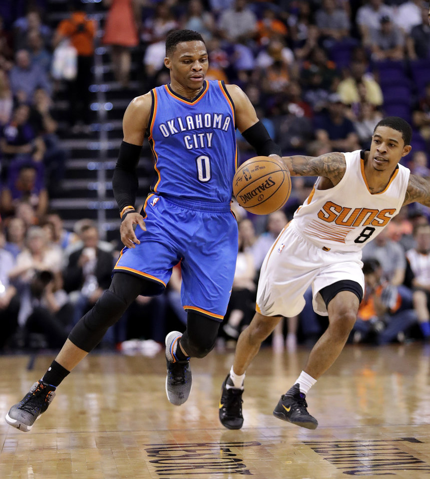 Photo - Oklahoma City Thunder guard Russell Westbrook (0) and Phoenix Suns guard Tyler Ulis (8) battle or the ball during the first half of an NBA basketball game, Friday, April 7, 2017, in Phoenix. (AP Photo/Matt York)