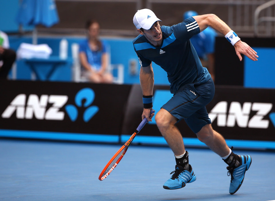 Photo - Andy Murray of BritaiN rushes for a return shot to Feliciano Lopez of Spain during their third round match at the Australian Open tennis championship in Melbourne, Australia, Saturday, Jan. 18, 2014.(AP Photo/Rick Rycroft)