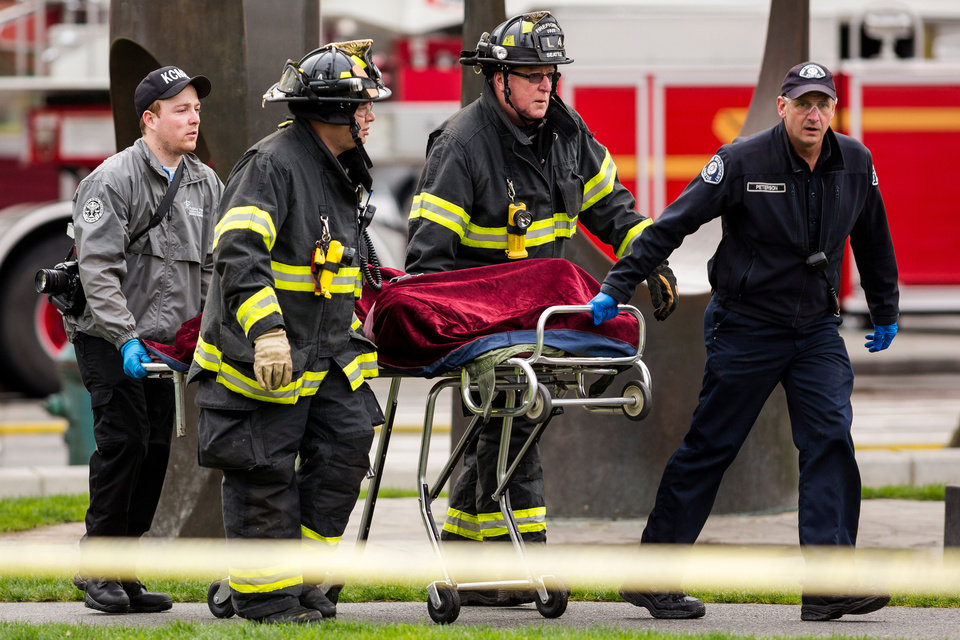 Photo - Emergency personnel wheel away one of two bodies from the aftermath of a news helicopter crash Tuesday, March 18, 2014, in Seattle, Wash. A KOMO-TV helicopter crashed into a city street near Seattle's Space Needle, killing two people and critically injuring a person in a car on the ground. (AP Photo/seattlepi.com, Jordan Stead) MAGS OUT; NO SALES; SEATTLE TIMES OUT; MANDATORY CREDIT; TV OUT