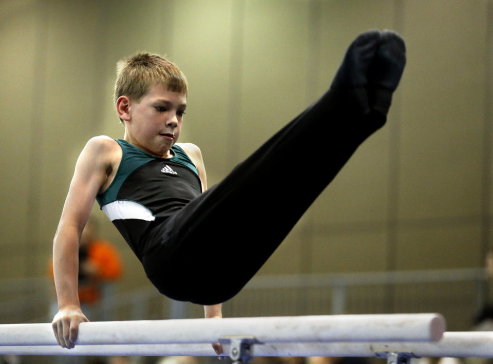 Photo - James Reynolds, 9, with Dynamo gymnastics in Oklahoma City competes in the bars at the Bart Connor Invitational Sports Festival on Saturday, Feb. 16, 2013  in Oklahoma City, Okla. Photo by Steve Sisney, The Oklahoman