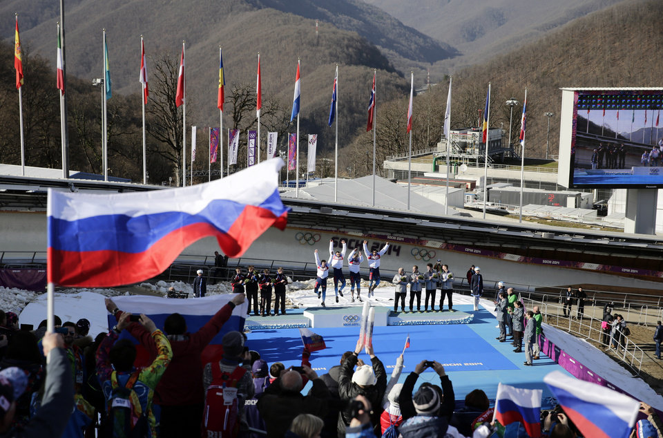 Photo - The team from Russia RUS-1, with Alexander Zubkov, Alexey Negodaylo, Dmitry Trunenkov, and Alexey Voevoda, jump onto the medal stand after they won the gold medal during the men's four-man bobsled competition final at the 2014 Winter Olympics, Sunday, Feb. 23, 2014, in Krasnaya Polyana, Russia. (AP Photo/Jae C. Hong)