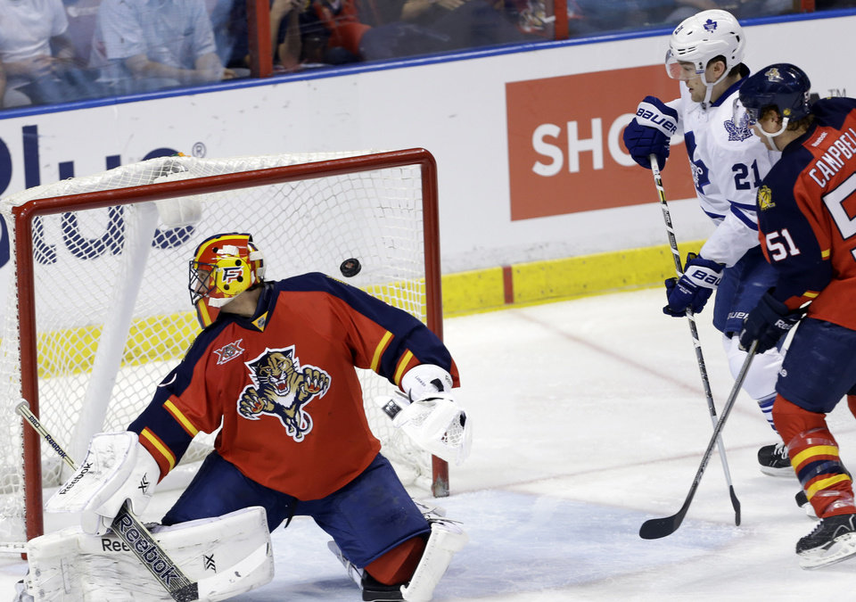 Photo - The puck gets past Florida Panthers goalie Roberto Luongo, left, on a goal scored by Toronto Maple Leafs' Tyler Bozak (not shown) in the second period of an NHL hockey game on Thursday, April 10, 2014, in Sunrise, Fla. Maple Leafs' James van Riemsdyk (21) and Florida Panthers' Brian Campbell (51) look on. (AP Photo/Lynne Sladky)
