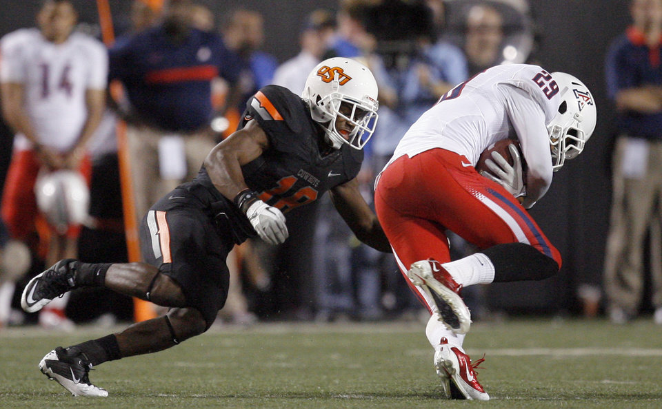 Photo - Oklahoma State's Devin Hedgepeth looks to tackle Arizona's Austin Hill (29) during their game Thursday in Stillwater. PHOTO BY SARAH PHIPPS, The Oklahoman