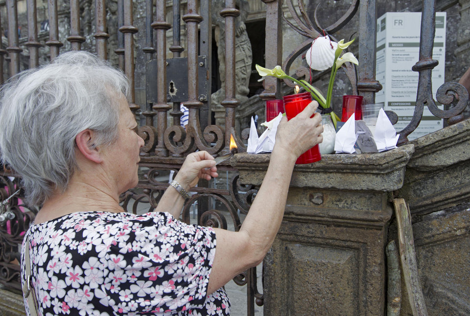 "Photo - A woman places a candle on the outside of the cathedral for the victims of the train accident in Santiago de Compostela, Spain, Friday July 26, 2013. Investigators have taken possession of the ""black boxes"" of the Spanish train that hurtled at high-speed along a curve and derailed, killing 80 people, a court official said Friday. Analysis will be performed to determine why the train was traveling far above the speed limit when it crashed near a station in Santiago de Compostela, in the northwestern Galicia region, said court spokeswoman Maria Pardo Rios. The train's operator remained hospitalised Friday and will be questioned by police but she said the interview will not happen Friday. (AP Photo/Lalo R. Villar)"