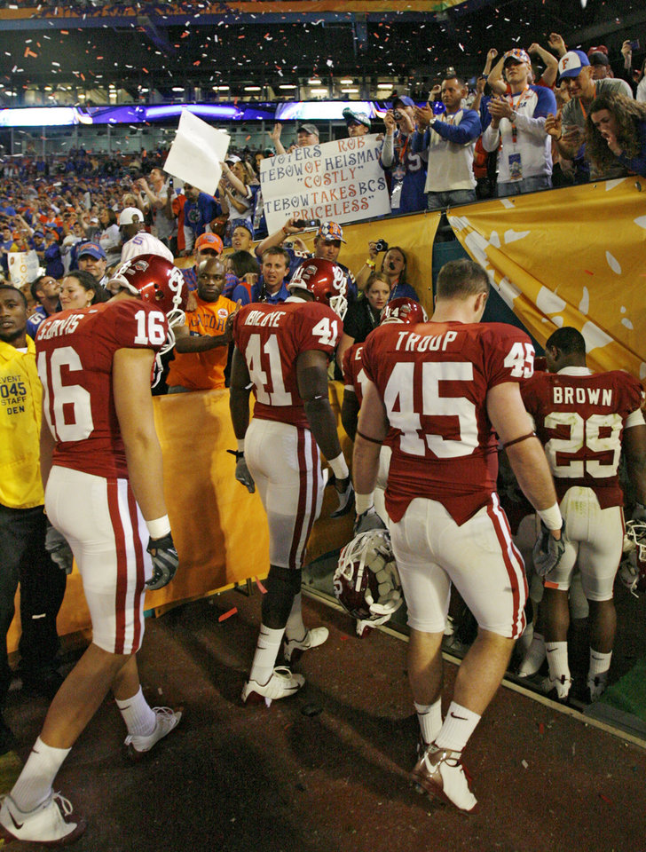 Photo - Oklahoma walks off the field as Florida fans celebrate in the stands after the BCS National Championship college football game between the University of Oklahoma Sooners (OU) and the University of Florida Gators (UF) on Thursday, Jan. 8, 2009, at Dolphin Stadium in Miami Gardens, Fla. Oklahoma lost the game 24-14 to the Gators.