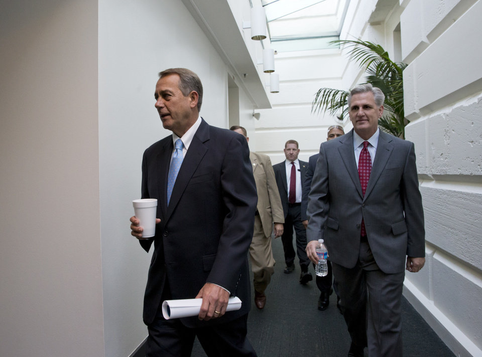 Photo - Speaker of the House John Boehner, R-Ohio, with House Majority Whip Kevin McCarthy, R-Calif., right, walks to a meeting of House Republicans at the Capitol in Washington, Tuesday, Oct. 15, 2013, as a partial government shutdown enters its third week. It is not yet clear how Boehner and tea party members in the House majority will respond to the Senate's Democratic and Republican leaders closing in on a deal to avoid an economy-menacing Treasury default and end the partial government shutdown.  (AP Photo/J. Scott Applewhite)