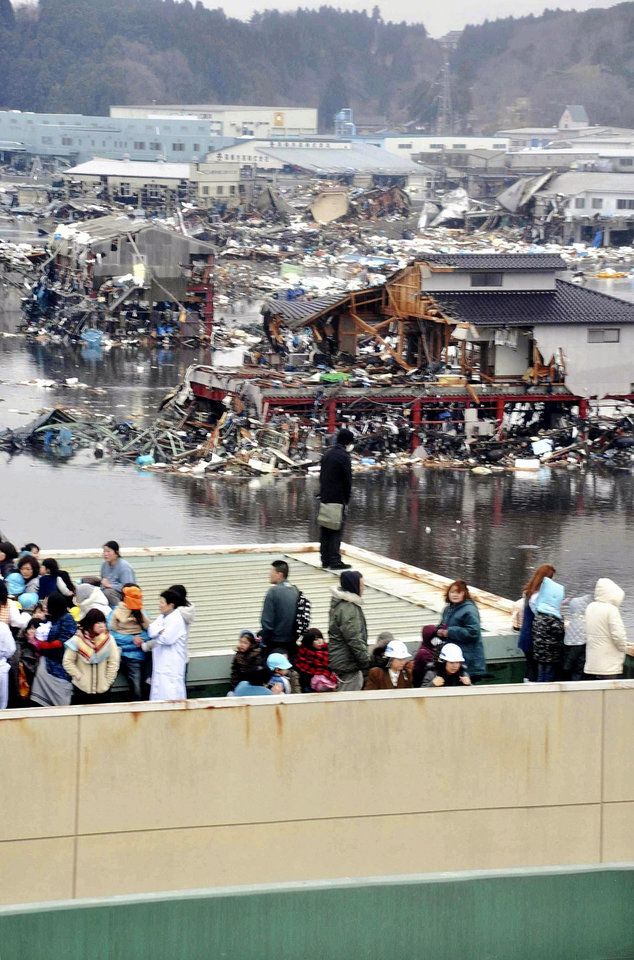 Photo - People evacuated to a rooftop of a building look at other buildings damaged by tsunami tidal waves at a port in  Kesennuma in Miyagi Prefecture, northern Japan, after strong earthquakes hit the area Friday, March 11, 2011. (AP Photo/Keichi Nakane, The Yomiuri Shimbun)  JAPAN OUT, CREDIT MANDATORY ORG XMIT: TOK829