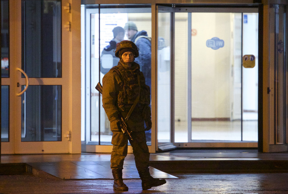Photo - An unidentified armed man patrols a square in front of the airport in Simferopol, Ukraine, Friday, Feb. 28, 2014.  Dozens of armed men in military uniforms without markings occupied the airport in the capital of Ukraine's strategic Crimea region early Friday. (AP Photo/Ivan Sekretarev)