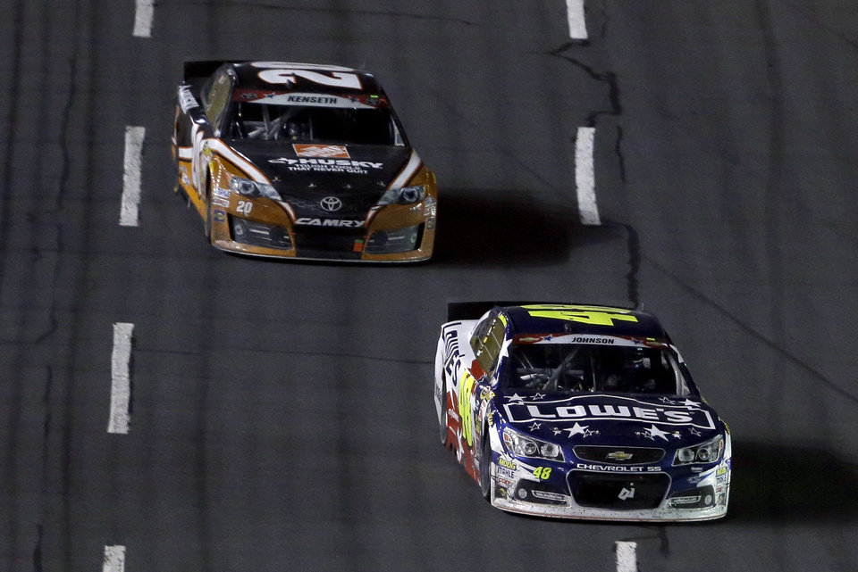 Photo - Jimmie Johnson (48) leads Matt Kenseth (20) down the front stretch in the closing laps of the NASCAR Sprint Cup series Coca-Cola 600 auto race at the Charlotte Motor Speedway in Concord, N.C., Sunday, May 25, 2014. Johnson won the race. (AP Photo/Gerry Broome)