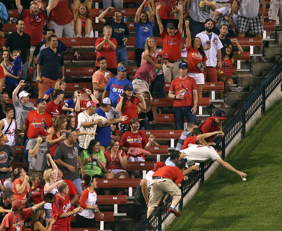 Photo - Fans scramble for St. Louis Cardinal Matt Holliday's second home run of the game to the batter's eye in center field in eighth inning action during a game between the St. Louis Cardinals and the Chicago Cubs on Saturday, Aug. 30, 2014, at Busch Stadium in St. Louis.  (AP Photo/St. Louis Post-Dispatch, Chris Lee)