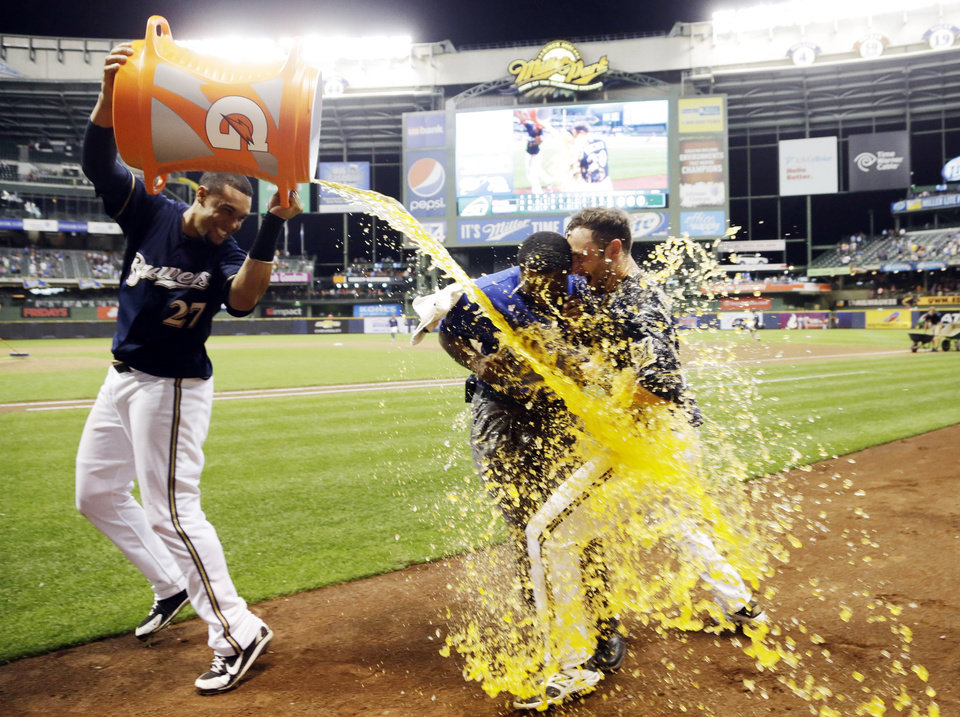 Photo - Milwaukee Brewers' Carlos Gomez dunks teammate Jonathan Lucroy during an interview after Lucroy hit a walk off home run during the ninth inning of a baseball game against the Cincinnati Reds Tuesday, July 22, 2014, in Milwaukee. The Brewers won 4-3. (AP Photo/Morry Gash)